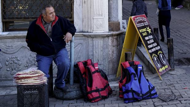 Un vendedor de chalecos para inmigrantes en una calle de Esmirna (Turquía)