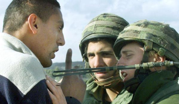 Un palestino discute con soldados israelíes en un control militar en las afueras de Ramala, Cisjordania