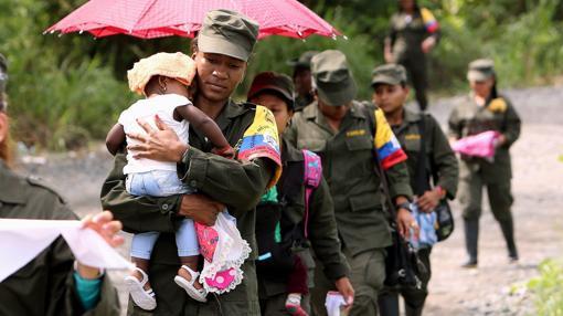 Mujeres de la guerrilla de las Fuerzas Armadas Revolucionarias de Colombia (FARC) marchan con sus hijos desde su campamento transitorio hacía una zona veredal