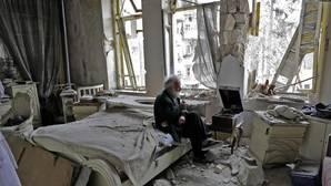 Un anciano fuma en pipa en los restos de su vivienda en Alepo