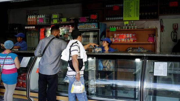 Un grupo de personas espera para comprar pan en un comercio de Caracas, el pasado 17 de marzo