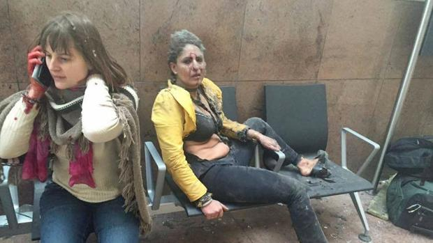 Foto que dio la vuelta al mundo que muestra a una mujer herida mirando como otra habla por su teléfono móvil después de las explosiones en el aeropuerto de Bruselas en Zaventem