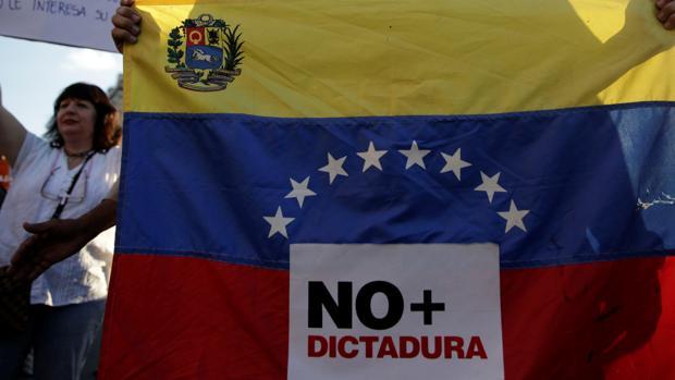 Un joven porta una bandera en una protesta en Caracas en la que se lee «No más dictadura»