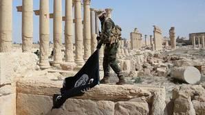 Imagen de archivo de un soldado sirio quita una bandera del «califato» en las ruinas