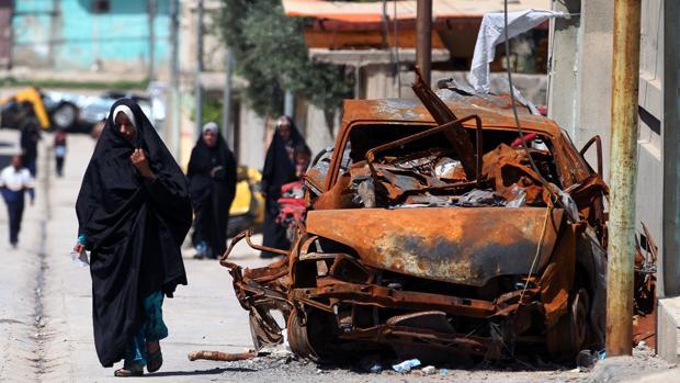 Una mujer camina al lado de un coche destruido por un atentado del Daesh en Irak