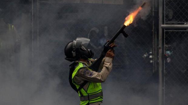 Un agente de la Guardia Nacional Bolivariana bloquea una marcha opositora con gases lacrimógenos, el pasado jueves en Caracas
