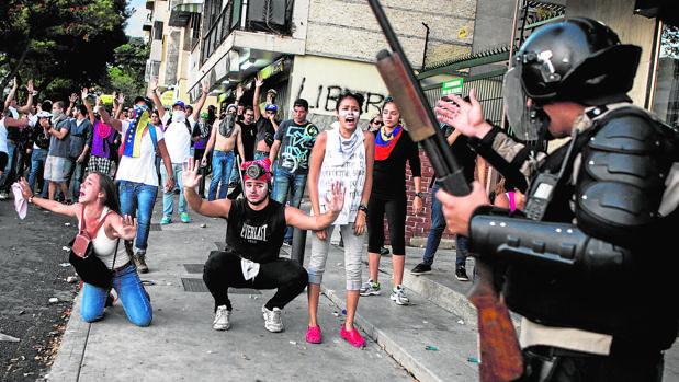 Fotografía de archivo que muestra cómo miembros de la Policía Nacional Bolivariana (PNB) enfrentan a manifestantes en la Plaza Altamira, en Caracas