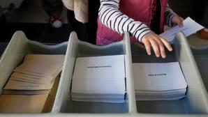 Una mujer escoge el sobre para votar en Marsella, Francia
