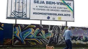 Un hombre pasa por delante de un cartel que refleja a Lula en la cárcel