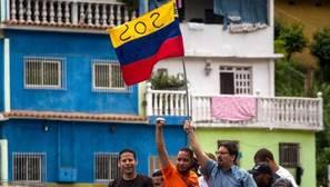 Freddy Guevara, vicepresidente de la Asamblea Nacional (c-d), sostiene una bandera durante una manifestación el sábado en Caracas