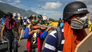 Un hombre toca el violín mientras participa en una marcha antigubernamental
