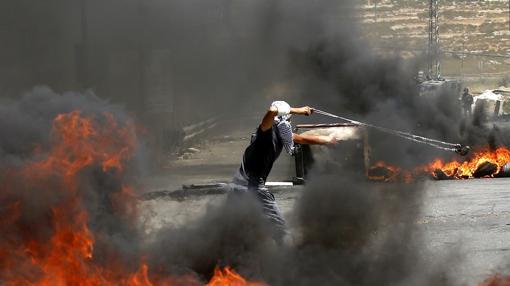 Un palestino lanza una piedra a tropas israelíes durante los disturbios por las celebraciones del día del Nakba en la ciudad cisjordana de Ramala (Palestina) hoy, 15 de mayo de 2017.