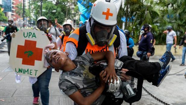 Un equipo de emergencia traslada a un adolescente afectado por los gases lacrimógenos durante una protesta opositora el martes en Caracas
