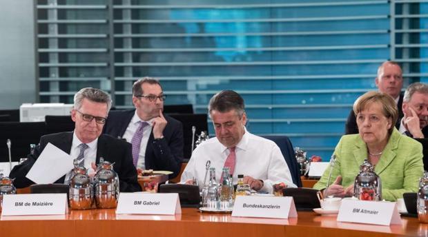 Angela Merkel, con Thomas de Maiziere (i) y Sigmar Gabriel (c), durante una reunión en la Cancillería con los dirigentes de los estados federados, este jueves en Berlín