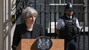 Un policía escuchaba atentamente a Theresa May durante su comparecencia