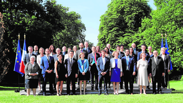 El presidente francés posa con su equipo de gobierno en pleno y el logo del París olímpico en las manos