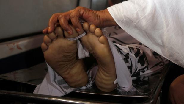 Una madre de un policía, que fue asesinado junto con tres de sus compañeros en un ataque con armas de fuego, toca los pies de su hijo mientras transportaba su cuerpo en una ambulancia fuera de una morgue de un hospital en Karachi, Pakistán