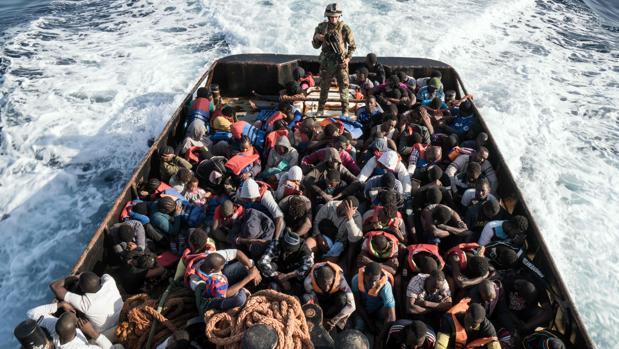 Un guardacostas libio, en pie abordo de un bote durante el rescate de 147 migrantes que se dirigían a Europa