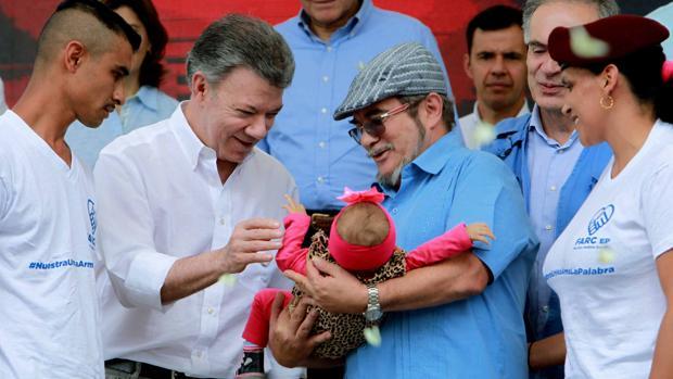 El presidente colombiano, Juan Manuel Santos, saluda a una bebé que sostiene el líder de las FARC, «Timochenko», en la ceremonia de dejación de armas en la zona veredal transitoria de normalización de Buenavista