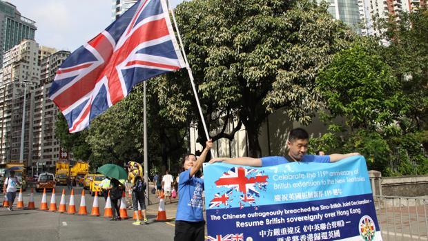 """Alice Lai, hongkonesa con una ciudadanía británica especial, ondea una """"Union Jack"""" en la manifestación por la democracia en el vigésimo aniversario de la devolución a China"""
