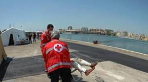 Trabajadores de la Cruz Roja ayudan a desembarcar a los 402 inmigrantes rescatados en el Mediterraáneo a su llegada al puerto de Brindisi (Italia)