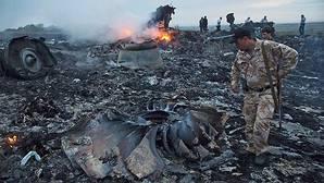 Un soldado inspecciona los restos del avión derribado en julio de 2014