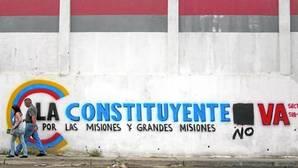 Una pareja pasa junto a una pared con propaganda a favor de la Constituyente, sobre la que hay una pintada opositora este sábado en Caracas