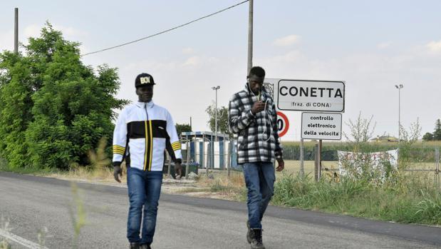 Los migrantes caminan por un sendero cerca del centro de acogida de Cona, cerca de Padua