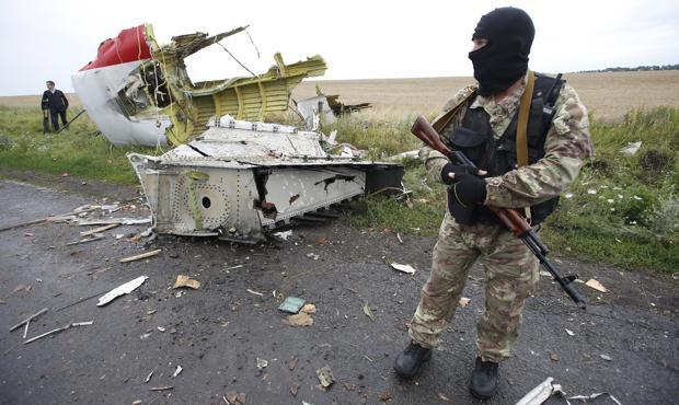 Un separatista prorruso permanece junto al los restos del avión que fue derribado por un misil de fabricación rusa el 17 de julio de 2014, el vuelo MH17 de Malaysia Airlines