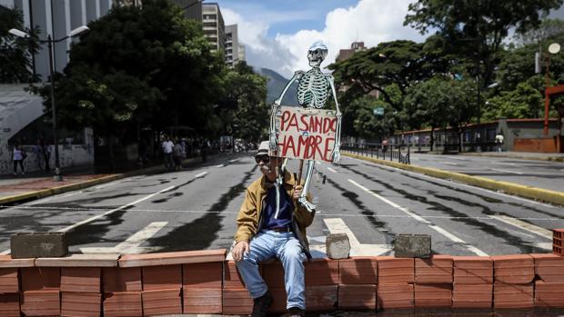 Un hombre protesta en una e las calles cortadas de Caracas