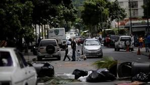 Un hombre y sus dos hijos caminan entre una barricada este sábado en Venezuela