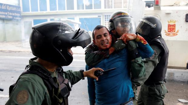Un grupo de policías bolivarianos detienen a un joven en el transcurso de una manifestación