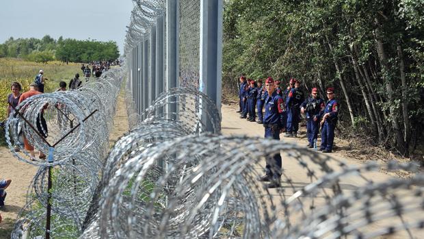 Un grupo de refugiados pasa frente al muro levantado por Hungría para impedir la llegada de migrantes