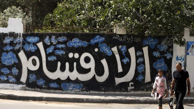 Un palestino y su hija pasan delante de un mural en Gaza en el que se lee «División»