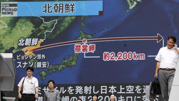 Japoneses caminan bajo un monitor a gran escala que muestra el vuelo de un misil balístico norcoreano