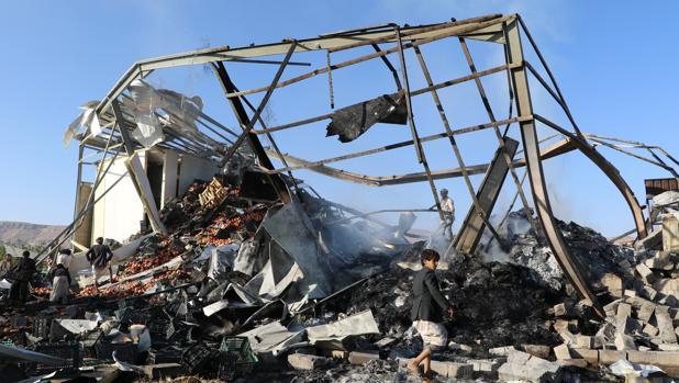 Ciudadanos tratan de trasladar la fruta de un edificio destruido por el ataque de la aviación saudí