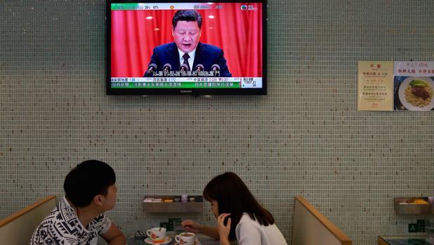 Una pareja almuerza en un café en Hong Kong bajo una televisión que muestra al presidente de China, Xi Jinping