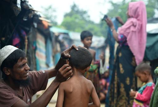 Un padre corta el pelo a su hijo en un campemento de refugiados
