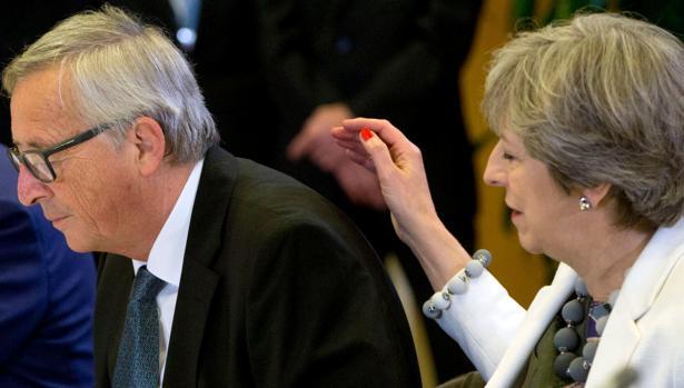 Theresa May pasa la mano por la espalda de Jean Claude Juncker el pasado día 20 en la cumbre europea