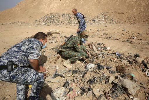 Soldados iraquíes examinan la fosa común con 500 cadáveres, pertenecietes a los presos de Badush