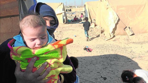 La viuda de un yihadista muestra a su hijo en el campo de internamiento de Shehama
