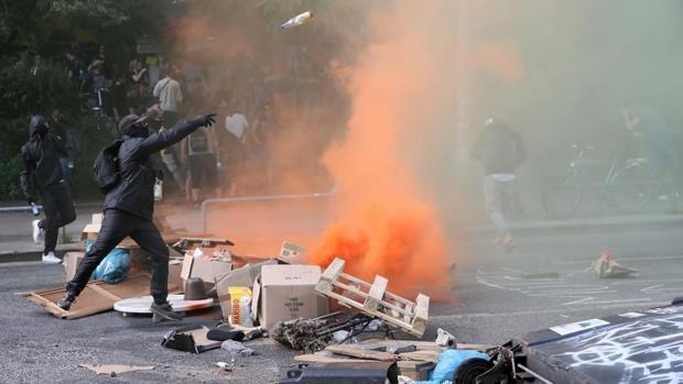 Un manifestante lanza una botella a la policía en los disturbios en Hamburgo, el pasado mes de julio