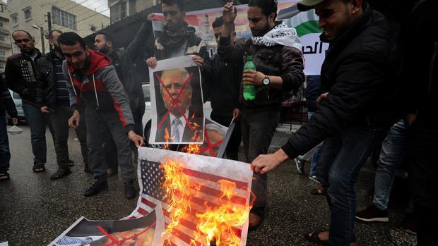 Palestinos queman una bandera estadounidense y retratos del presidente Trump, durante una protesta contra el reconocimiento de Jerusalén como capital de Israel