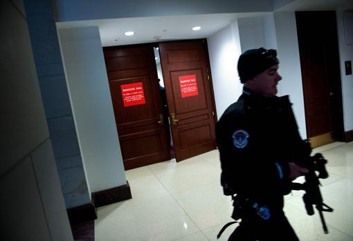 Un agente de seguridad vigila la puerta donde tiene lugar la declaración de Donald Trump Jr. ante el Congreso