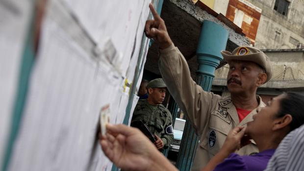 Electores comprueban su nombra en la lista de un colegio electoral en Caracas