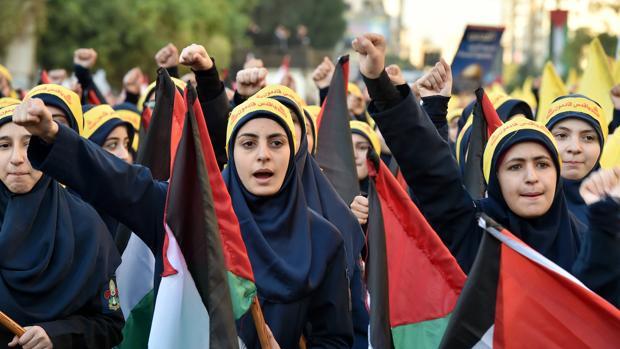 Mujeres libanesas, simpatizantes del grupo chií Hizbulá, ondean banderas palestinas durante una protesta en contra de la polémica decisión del presidente estadounidense, Donald Trump