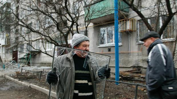Un hombre carga con una ventana rota después de que su vivienda fuera alcanzada por el bombardeo de rebeldes pro-rusos en la ciudad controlada de Yasinovátaya, en Donetsk