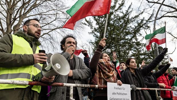 Manifestantes ondean banderas de la era de la monarquía constitucional iraní durante una protesta en la embaja de Irán en Berlín