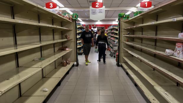 Varias personas buscan productos en un supermercado de Caracas