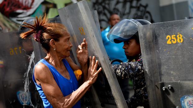 Fotografía de archivo en la que una mujer se enfrenta a los antidisturbios en una protesta contra la escasez de alimentos